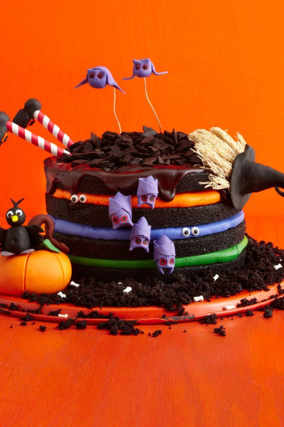 """<p>Colorful buttercream and edible fondant creatures turn a basic chocolate cake into something spooky and special.</p><p><strong><em><a href=""""https://www.womansday.com/food-recipes/food-drinks/recipes/a51843/black-chocolate-cake/"""" rel=""""nofollow noopener"""" target=""""_blank"""" data-ylk=""""slk:Get the Black Chocolate Witch Cake recipe."""" class=""""link rapid-noclick-resp"""">Get the Black Chocolate Witch Cake recipe. </a></em></strong> </p>"""