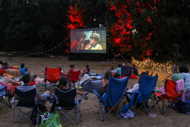 """FILE PHOTO: People watch the movie The Goonies at """"Sundown Cinema"""", an outdoor cinema which began during the coronavirus disease (COVID-19) outbreak, in a field in Ripley"""