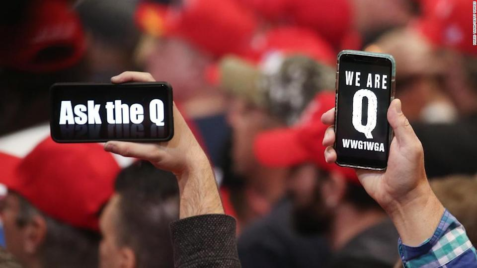 """<p>In this February 21, 2020, file photo, supporters of President Donald Trump hold up their phones with messages referring to the QAnon conspiracy theory at a campaign rally at the Las Vegas Convention Center. </p><div class=""""cnn--image__credit""""><em><small>Credit: Mario Tama/Getty Images / Getty Images</small></em></div>"""