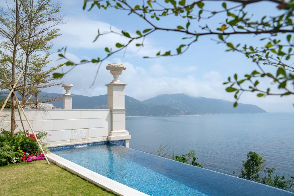An infinity swimming pool overlooks the sea at a house developed by National Electronics Holdings Ltd. and Baring Private Equity Asia Real Estate in Hong Kong, China, on Wednesday, Feb. 20, 2019. The cluster of homes nestled on a piece of land overlooking the South China Sea is the first property project National Managing Director Loewe Lee has overseen from start to finish. Five of the seven houses have been painstakingly fitted out with everything a modern multimillionaire could want. All a buyer need do is bring a suitcase, and $75 million (for one dwelling, that is). Photographer: Anthony Kwan/Bloomberg