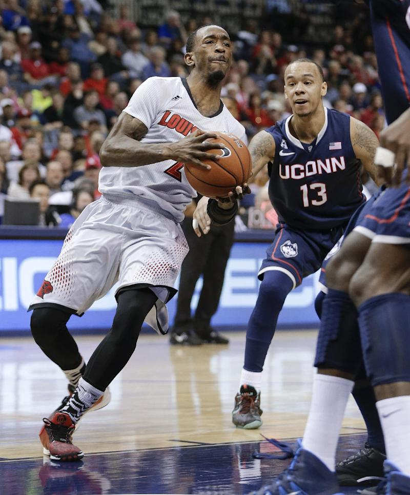 Louisville guard Russ Smith (2) drives past Connecticut guard Shabazz Napier (13) during the first half of an NCAA college basketball game in the finals of the American Athletic Conference men's tournament Saturday, March 15, 2014, in Memphis, Tenn. (AP Photo/Mark Humphrey)