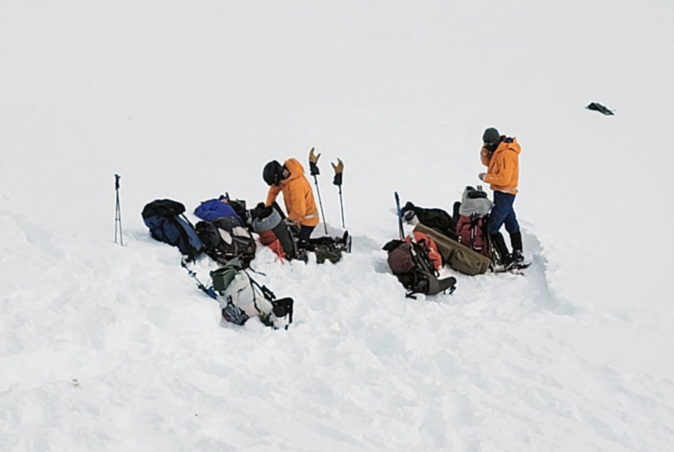 Volunteers of the Alaska Mountain Rescue Group work near the scene of the helicopter crash.