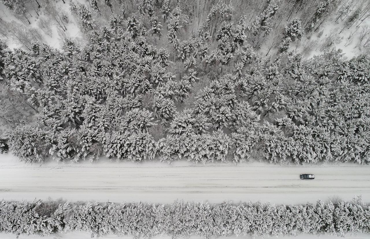 An aerial view shows a car driving along a forest road after snowfall outside Krasnoyarsk, Russia March 22, 2018. REUTERS/Ilya Naymushin     TPX IMAGES OF THE DAY