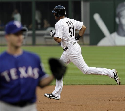 Chicago White Sox's Alex Rios rounds the bases after hitting a home run against Texas Rangers pitcher Roy Oswalt, left, during the first inning of a baseball game, Tuesday, July 3, 2012, in Chicago. (AP Photo/John Smierciak)