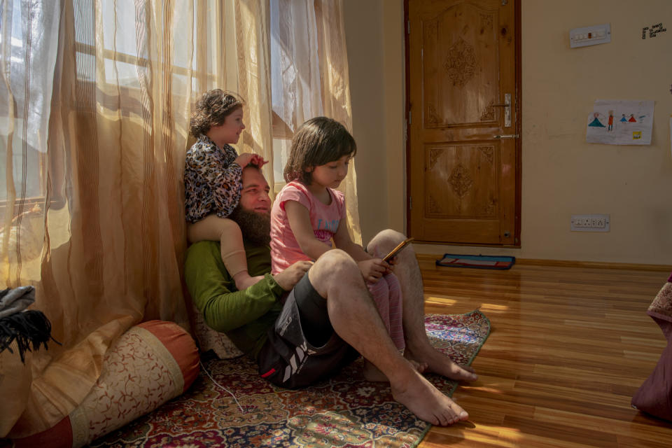 """Khalid Bazaz plays with his niece Sundas Irfan, as his daughter Maria Khalid sits on his lap and watches online classes, at their home in Srinagar, Indian controlled Kashmir, Thursday, July 23, 2020. Confined to their homes, students have found it challenging to study online with the painstakingly slow internet connections, which also faces outages following the frequent gunbattles between rebels and Indian soldiers. With no high-speed internet, many educators are unable to upload video lectures and conduct online classes. But some are making the best of limited resources. """"I have to spend 3 hours every day with Maria as she is too young to handle zoom meetings and like every child she is not interested in these online classes,"""" Khalid said. (AP Photo/Dar Yasin)"""