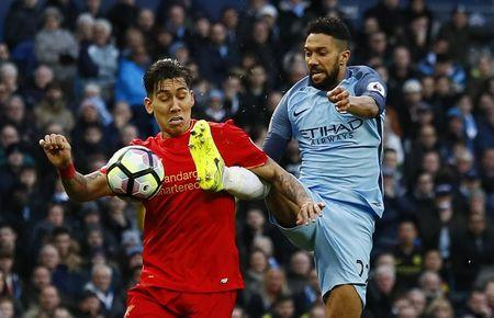 Manchester City's Gael Clichy fouls Liverpool's Roberto Firmino for a penalty
