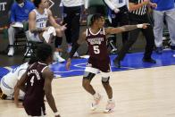 Mississippi State guard Cameron Matthews (4) looks on as guard Deivon Smith (5) celebrates sinking a basket in the first half of an NCAA college basketball against Memphis in the championship game in the NIT, Sunday, March 28, 2021, in Frisco, Texas. (AP Photo/Tony Gutierrez)