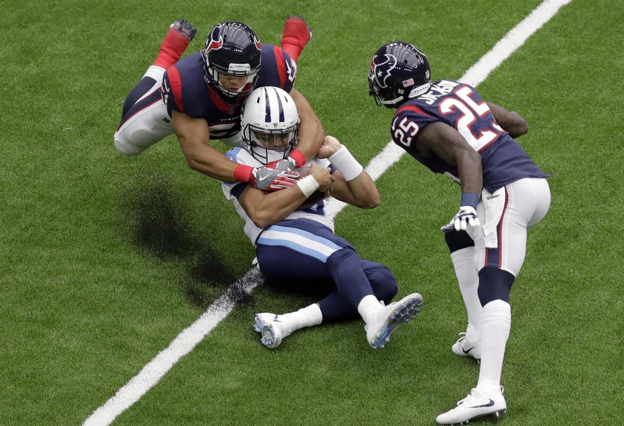<p>Tennessee Titans quarterback Marcus Mariota, center, is dropped by Houston Texans linebacker Dylan Cole (51) during the first half of an NFL football game, Sunday, Oct. 1, 2017, in Houston. (AP Photo/Eric Gay) </p>