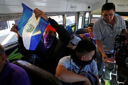 People in a caravan of migrants en route to the United States sit on a bus in San Salvador