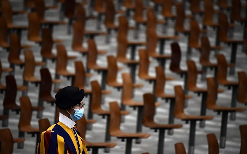 A Swiss guard wearing a face mask stands in an almost empty Paul Vi Hall during Pope Francis limited public audience at the Vatican on October 7 - FILIPPO MONTEFORTE/AFP