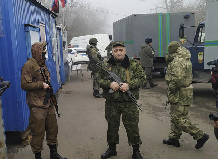 Russia-backed separatist soldiers stand guard near vehicles with Ukrainian war prisoners waiting to be exchanged near the checkpoint Horlivka, eastern Ukraine, Sunday, Dec. 29, 2019. Ukraine's president says his country expects to swap prisoners with Russia-backed separatists in the east on Sunday. (AP Photo/Alexei Alexandrov)