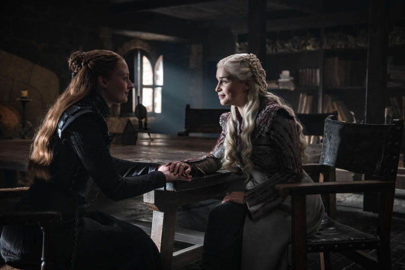 "This image released by HBO shows Sophie Turner, left, Emilia Clarke in a scene from ""Game of Thrones,"" that aired Sunday, April 21, 2019. With the Game of Thrones' Jon Snow revealing his royal lineage to his potential rival Daenerys Targaryen, the beleaguered army at Winterfell is about to find out if two chief executives better than one. (Helen Sloan/HBO via AP)"