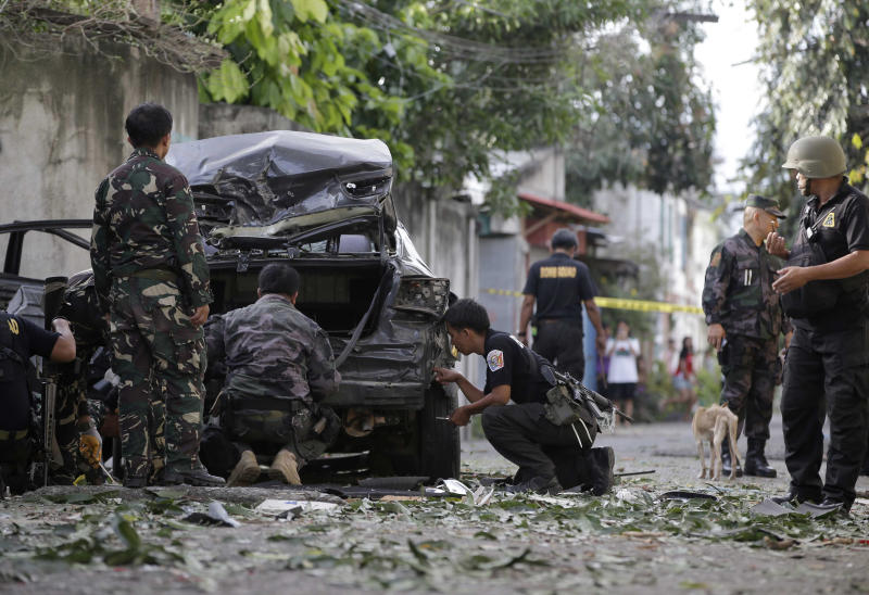 Police investigators examine the scene of an explosion as renewed fighting between Government forces and Muslim rebels, who have taken scores of hostages, enters its second week Monday Sept. 16, 2013 in Zamboanga city in the southern Philippines. The standoff, which began last Monday when about 200 Moro National Liberation Front guerrillas stormed several coastal communities in the city and seized several residents, has displaced more than 60,000, hundreds of homes razed to the ground, forced the closure of businesses and resulted in more than 50 deaths so far. (AP Photo/Bullit Marquez)