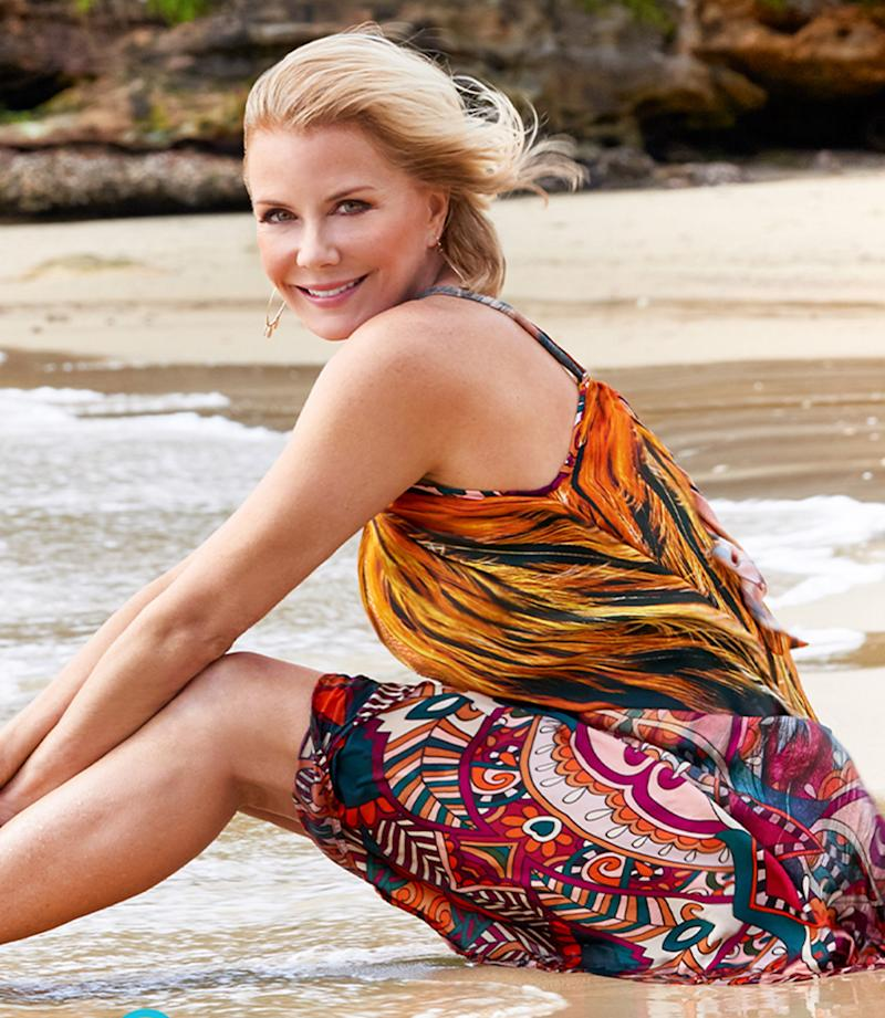 A photo of Katherine Kelly Lang wearing a colourful dress and posing on the beach.