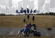 Photographers lie on the ground to take the best picture as Nurse Angela Helleur, right, is guided through Luke Jerram's In Memoriam art installation that was erected outside the Queen Elizabeth Hospital on Woolwich Common in London, Saturday, Aug. 29, 2020. It has been created as a memorial to those lost in the Covid-19 pandemic as well a tribute to the NHS and care-workers. Created from bed sheets, In Memoriam is intended to be an evocative symbol of local, national and international solidarity, presented as a space for reflection, remembrance, and recognition.(AP Photo/Frank Augstein)