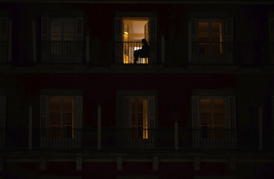 A woman sits on the balcony of her home on the Mayor square in downtown Madrid, Spain, Friday, Oct. 23, 2020. In much of Europe, city squares and streets, be they wide, elegant boulevards like in Paris or cobblestoned alleys in Rome, serve as animated evening extensions of drawing rooms and living rooms. As Coronavirus restrictions once again put limitations on how we live and socialize, AP photographers across Europe delivered a snapshot of how Friday evening, the gateway to the weekend, looks and feels. (AP Photo/Manu Fernandez)
