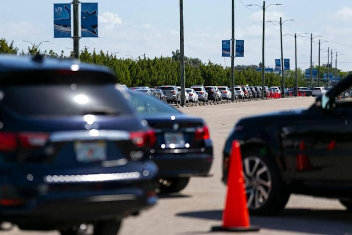 A long line of cars forms as people arrive at the Miami Dade College North vaccination site in Miami, Florida, to try and receive a COVID-19 vaccine on Sunday, March 7, 2021.