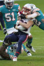 New England Patriots wide receiver Gunner Olszewski (80) is tackled by Miami Dolphins defensive back Clayton Fejedelem (42), right, and linebacker Sam Eguavoen (49), during the first half of an NFL football game, Sunday, Dec. 20, 2020, in Miami Gardens, Fla. (AP Photo/Chris O'Meara)