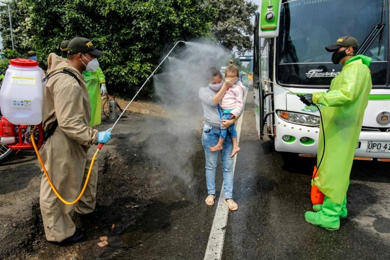 Colombian border police sprayed disinfectant on Venezuelan migrants returing home to prevent the spread of the deadly novel coronavirus (AFP Photo/Schneyder MENDOZA)