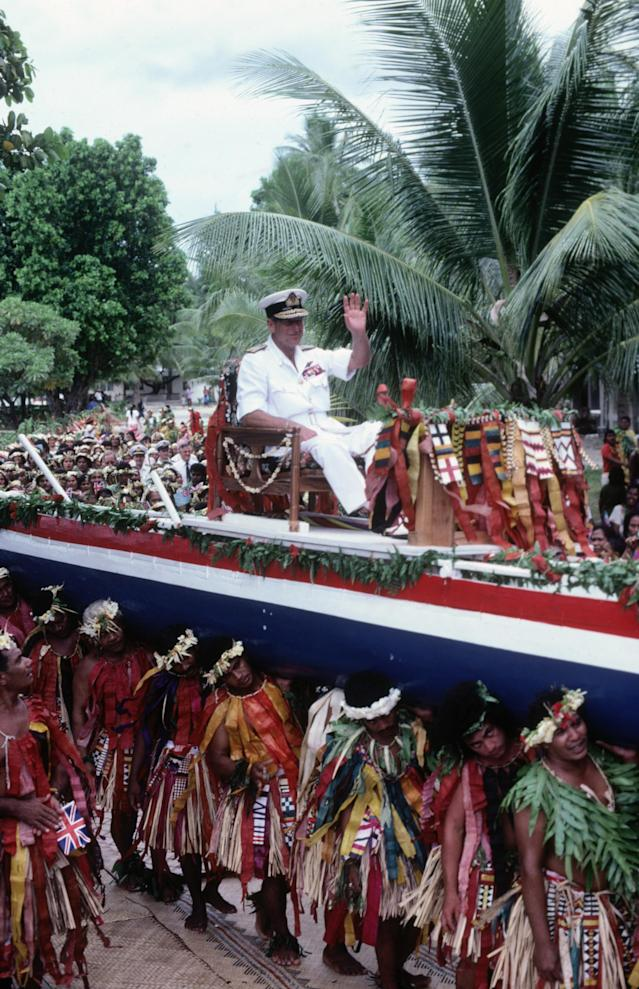 Prince Philip carried aloft on a canoe through the streets of the Pacific island of Tuvalu in 1982 during the Royal Tour of the South Pacific. (David Levenson/Getty Images)
