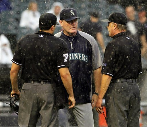 Seattle Mariners' manager Eric Wedge, center, questions home plate umpire Jim Reynolds, left, and Jim Joyce, right, on their call to delay the baseball game against the Chicago White Sox for rain in the seventh inning, Sunday, Aug. 26, 2012, in Chicago. (AP Photo/John Smierciak)