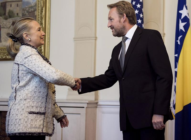 US Secretary of State Hillary Rodham Clinton, left, shakes hands with Bakir Izetbegovic, Chairman of the Bosnia and Herzegovina Tri-Presidency, prior to meetings at the Presidencyin Sarajevo, Bosnia, Tuesday, Oct. 30, 2012. The top American and European diplomats are on a joint diplomatic tour of the Balkans, urging rival ethnic groups and governments in Bosnia, Serbia and Kosovo to settle their differences for the good of their nations. U.S. Secretary of State Hillary Rodham Clinton was talking Tuesday with European Union foreign policy chief Catherine Ashton in the Bosnian capital of Sarajevo. They are then meeting together with Bosnia's three presidents before travelling to Belgrade for similar talks with Serbian leaders. Clinton and Ashton will see Kosovo's leaders on Wednesday. (AP Photo/Saul Loeb, Pool)