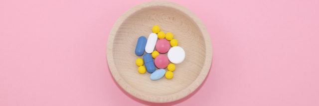 Different kinds of pharmaceutical tablets on pink paper background.