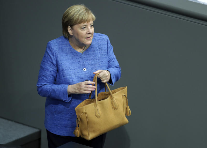 German Chancellor Angela Merkel holds her bag as she arrives for a meeting of the German federal parliament, Bundestag, at the Reichstag building in Berlin, Germany, Wednesday, Sept. 11, 2019. (AP Photo/Michael Sohn)