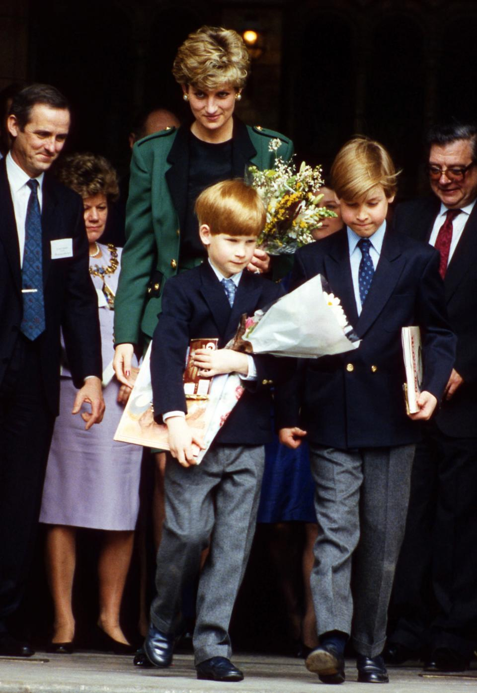 """FILE - In this April 13, 1992 file photo, Princess Diana leaves the Natural History Museum after a dinosaur exhibition with her sons Prince Harry, left, and Prince William. For someone who began her life in the spotlight as """"Shy Di,"""" Princess Diana became an unlikely, revolutionary during her years in the House of Windsor. She helped modernize the monarchy by making it more personal, changing the way the royal family related to people. By interacting more intimately with the public -- kneeling to the level of children, sitting on edge of a patient's hospital bed, writing personal notes to her fans -- she set an example that has been followed by other royals as the monarchy worked to become more human and remain relevant in the 21st century. (AP Photo/Gill Allen, File)"""