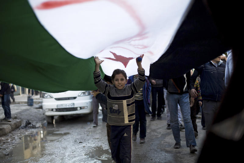A Syrian child marches under a revolutionary flag during a weekly demonstration in Aleppo, Syria, Friday, Dec. 14, 2012. (AP Photo/Manu Brabo)