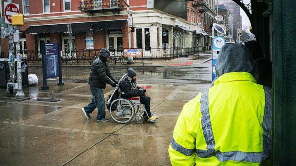 PHOTO: A man is pushed in his wheelchair to the Path train station where service operates on a weekend schedule due to the coronavirus outbreak, March 23, 2020, in Hoboken, N.J.  (Eduardo Munoz Alvarez/Getty Images)