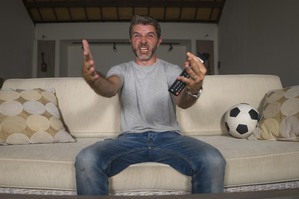 man wearing jeans and a grey t-shirt while watching a football game on television from the sofa in the living room. He is frustrated and angry his because his team is losing the game
