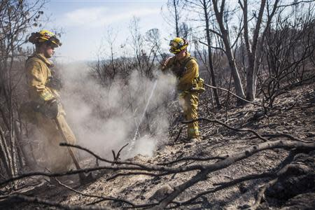 Redding Fire Department firefighters Gibbons and Smith mop up hot spots on the Clover Fire in Happy Valley, California