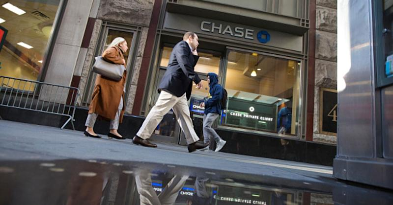 Pedestrians pass a JPMorgan Chase & Co. bank branch near the New York Stock Exchange in 2018.