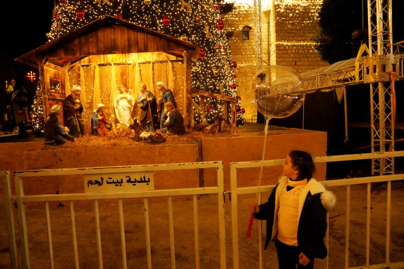 Girl looks at an artwork showing a nativity scene made of olive wood at Manger Square in Bethlehem in the Israeli-occupied West Bank