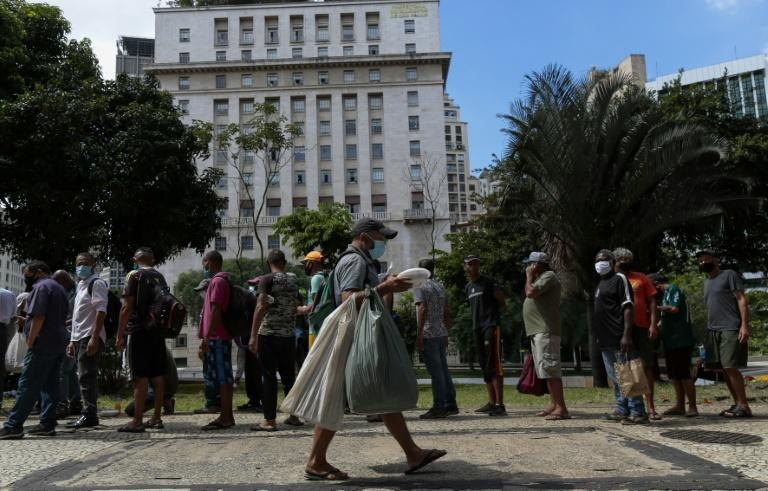 Homeless people queue to receive lunch in downtown in Sao Paulo, Brazil, on March 23, 2021