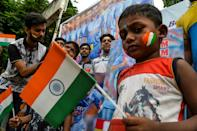 Indian fans get their faces painted with colours of the national flag (Photo by DIPTENDU DUTTA/AFP/Getty Images)