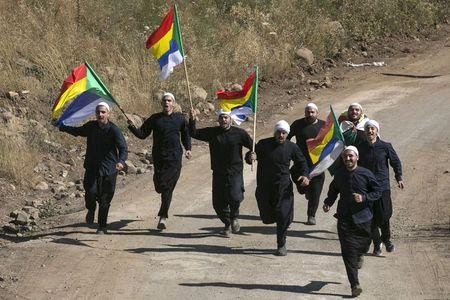 File photo of members of the Druze community carrying flags at they run towards the border fence between Syria and the Israeli-occupied Golan Heights