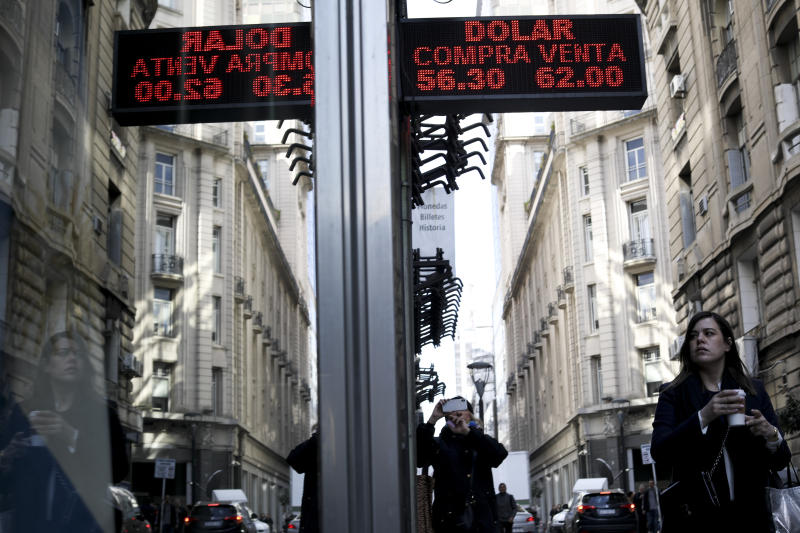 A woman walks under a sign showing exchange rates between the US dollar and Argentine peso in Buenos Aires, Argentina, Monday, Sept. 2, 2019. Argentina's government decreed on Sunday that Argentines will need authorization from the central bank for the rest of the year to buy U.S. dollars in some cases and make transfers abroad as it tries to prop up its peso currency, following a peso devaluation and ahead of an Oct. 27 election. (AP Photo/Natacha Pisarenko)