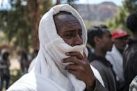 Men in Dengolat covered their faces to weep as women pounded the ground and showed images of their loved ones