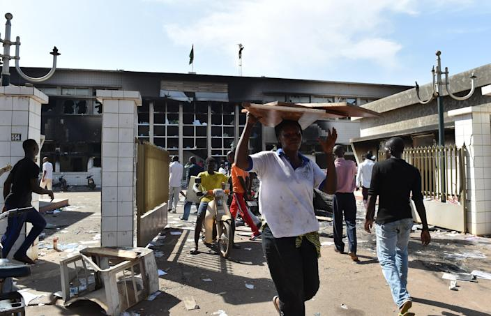 People loot on October 31, 2014 what is salvageable inside the burnt parliament in Ouagadougou a day after it was stormed by protesters (AFP Photo/Issouf Sanogo)