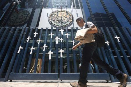 A man passes in front of crosses adhered to a fence during a protest against the murder of journalists in Mexico, outside the Attorney General's Office (PGR) in Mexico City