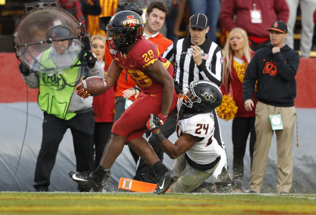 Iowa State running back Breece Hall, left, drives in a touchdown despite defensive efforts by Oklahoma State safety Jarrick Bernard, right, during the second half of an NCAA college football game, Saturday, Oct. 26, 2019, in Ames, Iowa. Oklahoma State won 34-27. (AP Photo/Matthew Putney)