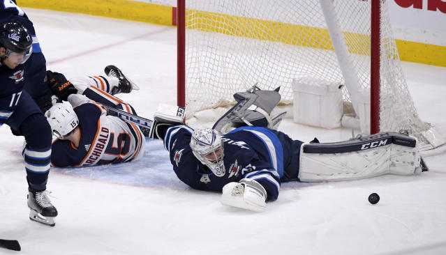 Winnipeg Jets' goaltender Connor Hellebuyck (37) makes a save as Edmonton Oilers' Josh Archibald (15) holds his stick during the first period of an NHL hockey game in Winnipeg, Manitoba, Sunday, Oct. 20, 2019. (Fred Greenslade/The Canadian Press via AP)
