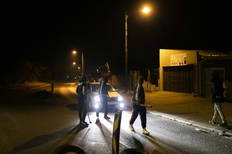 Vigilantes: Community members mount a road block in Phoenix Township. Twenty people have died in clashes