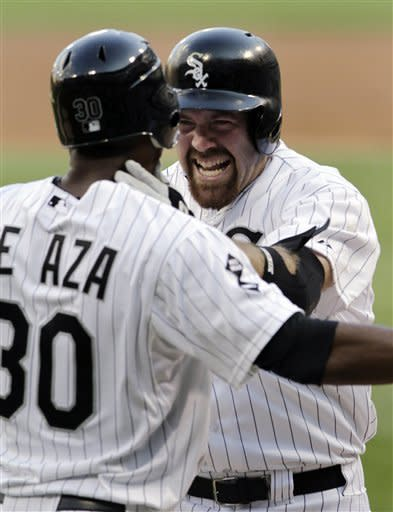 Chicago White Sox's Kevin Youkilis, right, celebrates with Alejandro De Aza as they scored on Youkilis' two-run home run against the Texas Rangers during the first inning of a baseball game, Tuesday, July 3, 2012, in Chicago. (AP Photo/John Smierciak)