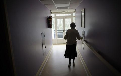 A woman suffering from Alzheimer's disease, walks in a corridor in a retirement house in Angervilliers, eastern France - Credit: SEBASTIEN BOZON/AFP