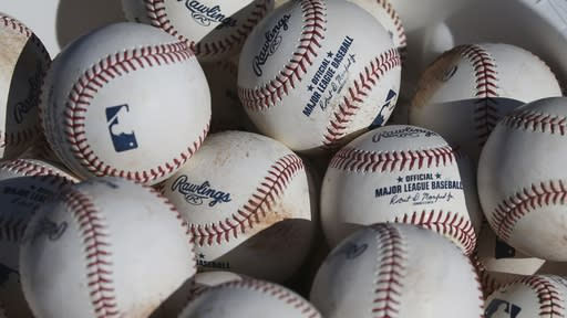 FILE - In this Feb. 14, 2020, file photo, baseballs occupy a bucket after use during fielding practice during spring training baseball workouts for pitchers and catchers at Cleveland Indians camp in Avondale, Ariz. Major League Baseball is suspending all political contributions in the wake of last week's invasion of the U.S. Capitol by a mob loyal to President Donald Trump, joining a wave of major corporations rethinking their efforts to lobby Washington. In light of the unprecedented events last week at the U.S. Capitol, MLB is suspending contributions from its Political Action Committee pending a review of our political contribution policy going forward, the league said in a statement to The Associated Press on Wednesday, Jan. 13, 2021. (AP Photo/Ross D. Franklin, File)
