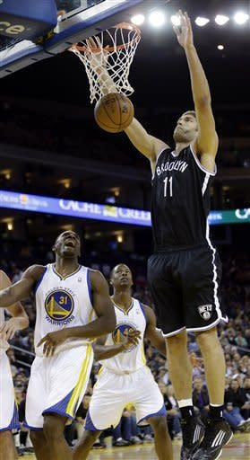 Brooklyn Nets' Brook Lopez (11) follows through on a shot next to Golden State Warriors' Festus Ezeli (31) during the first half of an NBA basketball game in Oakland, Calif., Wednesday, Nov. 21, 2012. (AP Photo/Marcio Jose Sanchez)