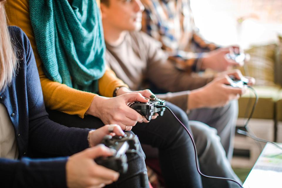 Multiple teens holding video game controllers while seated on a couch.